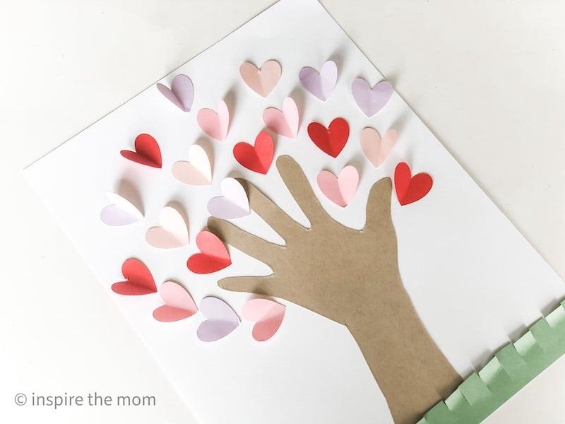 glueing hearts on the handprint heart tree